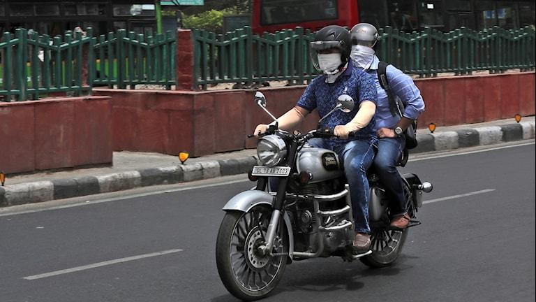 Smog i Indien får motorcykelchaufförer att täcka näsa och mun.