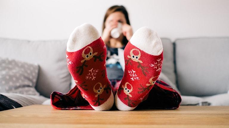 Bild på tjej med röda strumpor som sitter i en soffa och dricker kaffe.