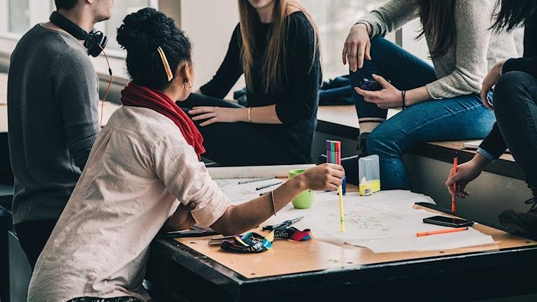 Studenter sitter vid ett bord.
