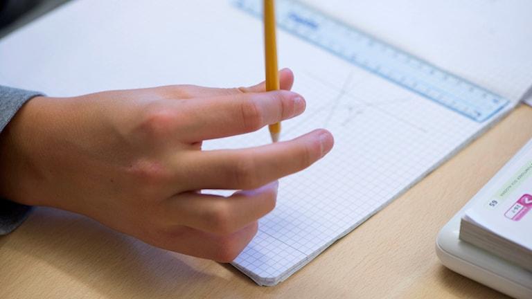 Hand håller i en penna över en mattebok