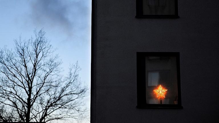 Husfasad med julstjärna i ett av fönstren.