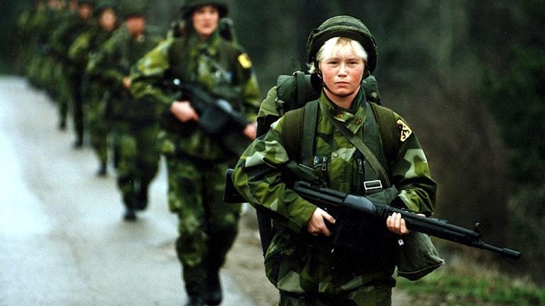 Soldater som marscherar med vapen, blond tjej i täten