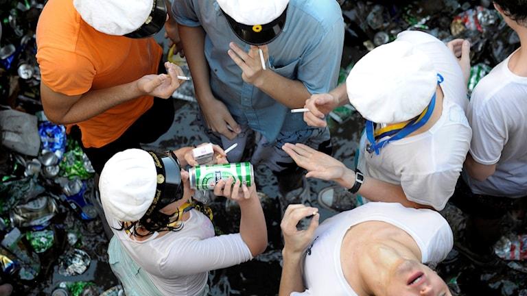 Studenter dricker öl och röker på ett studentflak.