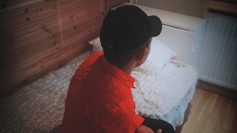 Bild på Kille som sitter bortvänd på en säng.
