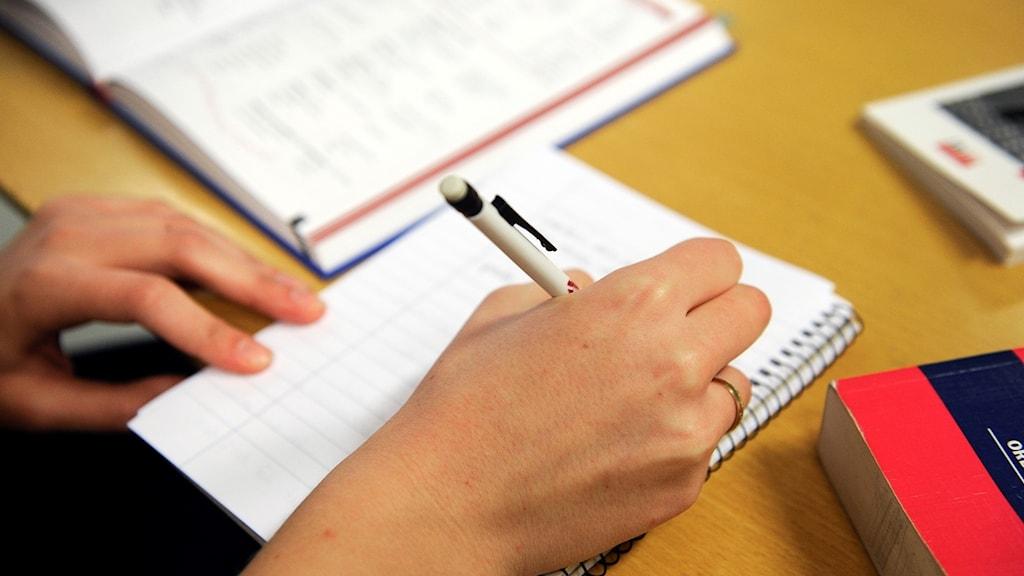 En person antecknar ur en lärobok. Foto: Anders Wiklund/TT.
