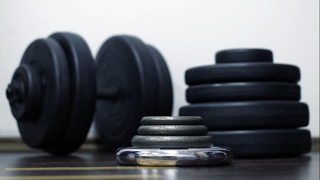 Bild på hantlar på ett gymgolv.