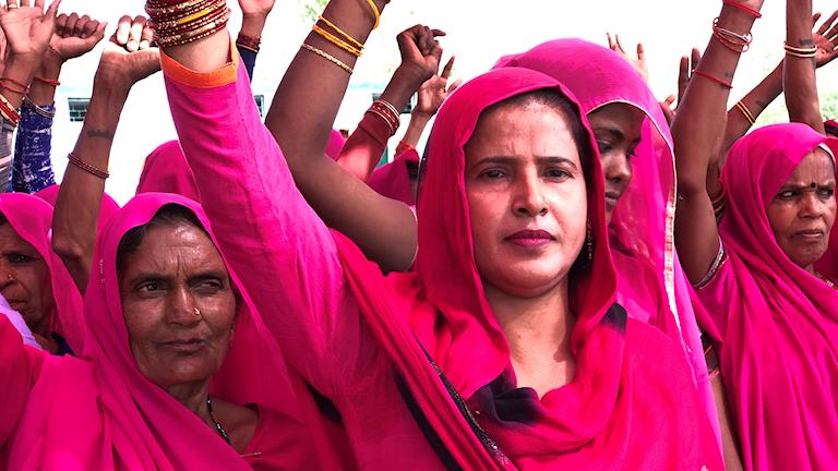 Grupp med rosaklädda kvinnor håller armarna i luften och tittar rakt fram.