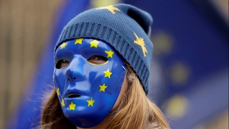Kvinnlig EU-supporter i en mask med EU-flaggan.