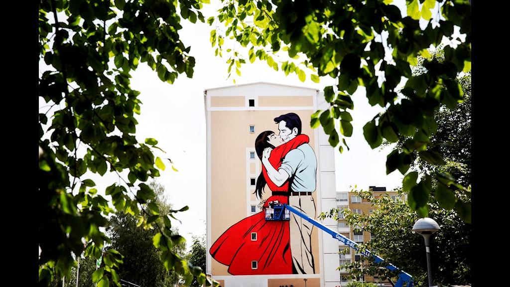 Målning på husvägg där en man och en kvinna omfamnar varandra.