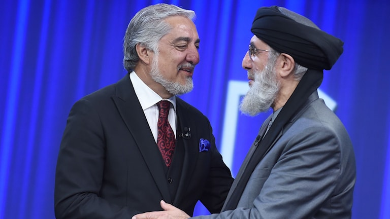 Afghan presidential candidates Abdullah Abdullah (L) and Gulbuddin Hekmatyar shake hands prior to take part in a presidential debate at Tolo News TV station in Kabul on September 26, 2019.