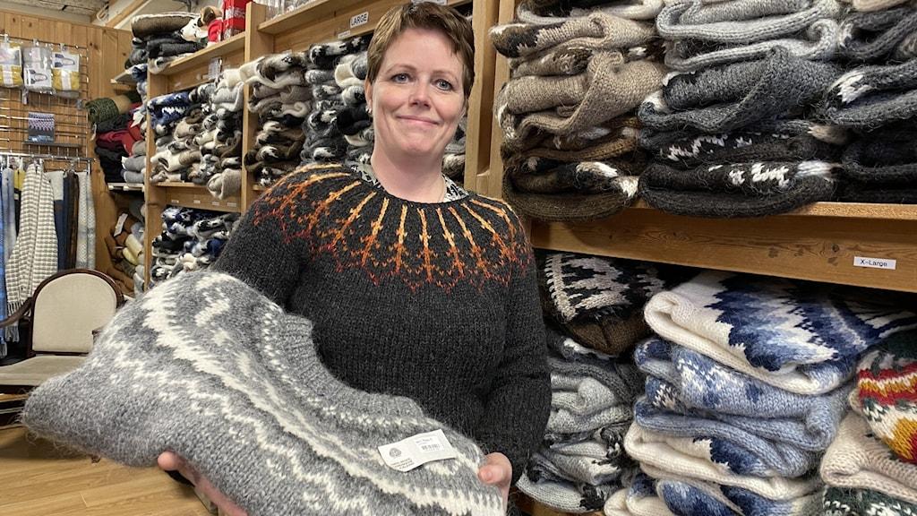 Kvinna håller en ulltröja i famnen.
