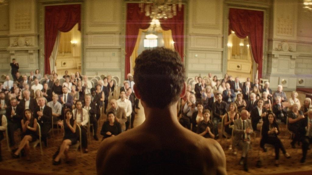 Man med ryggtavla står vänd mot en publik.