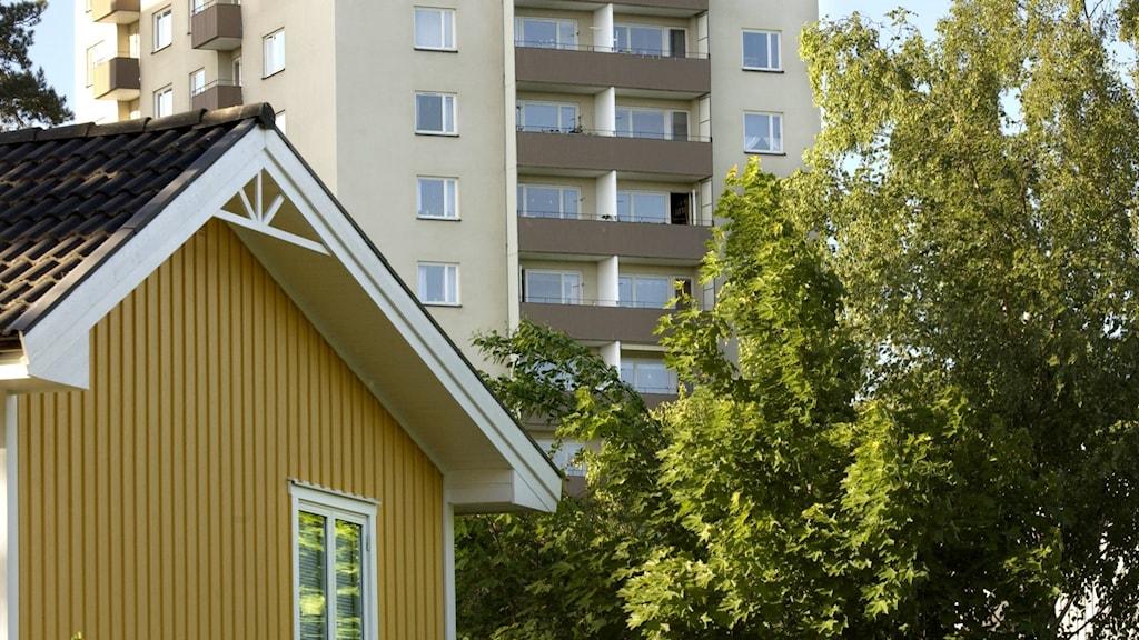 En gul villa med vita knutar med ett vitrappat betonghus i bakgrunden.