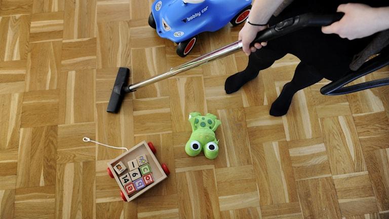 Person som dammsuger. Runt om ligger leksaker.