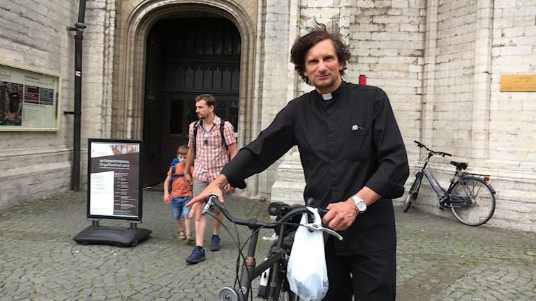 Rudi Mannearts, präst i Antwerpen  välkomnar turister till staden med specialskrivna turistbroschyrer.