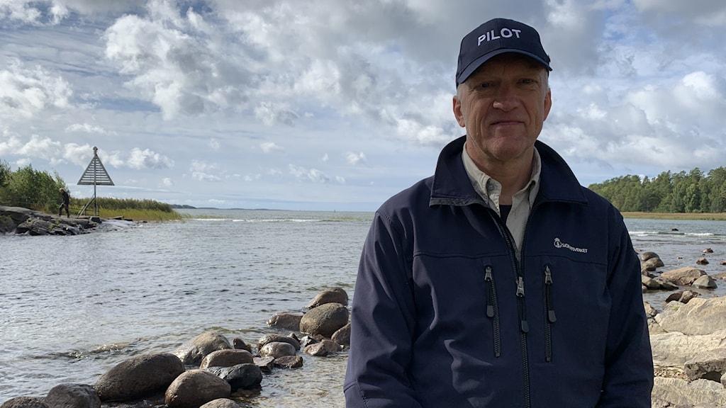 Lotsen Christer Eriksson har en blå jacka som det står Sjöfartsverket på och en blå keps. Han står vid Picassoskulpturen i Kristinehamn med Vänern i bakgrunden. Foto: Jonas Berglund/Sveriges Radio.