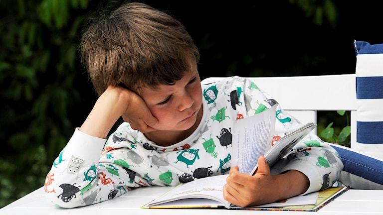 Ett barn som läser en bok. Foto: Hasse Holmberg/TT.