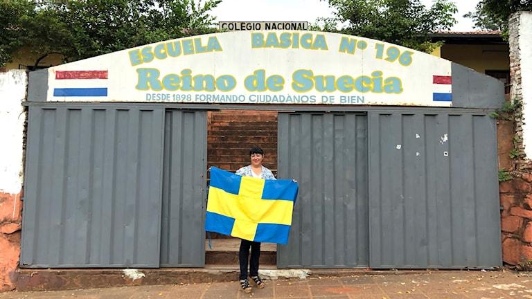 """Rektorn Luz Maria Rodriguez håller upp flaggan utanför entrén till skolan som svenska immigranter 1898 döpte till """"Kungariket Sverige""""."""