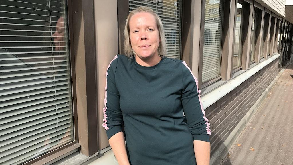 Kvinna i grön tröja framför fönster.
