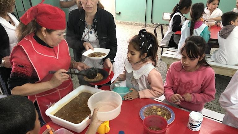 Kokerskan Teresa Briges slevar upp linsgryta till barnen på skolan i förorten Moreno, hårt drabbad av den argentinska krisen.
