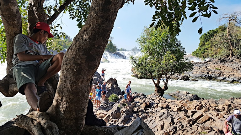 Turister blickar ut över ett vattenfall.