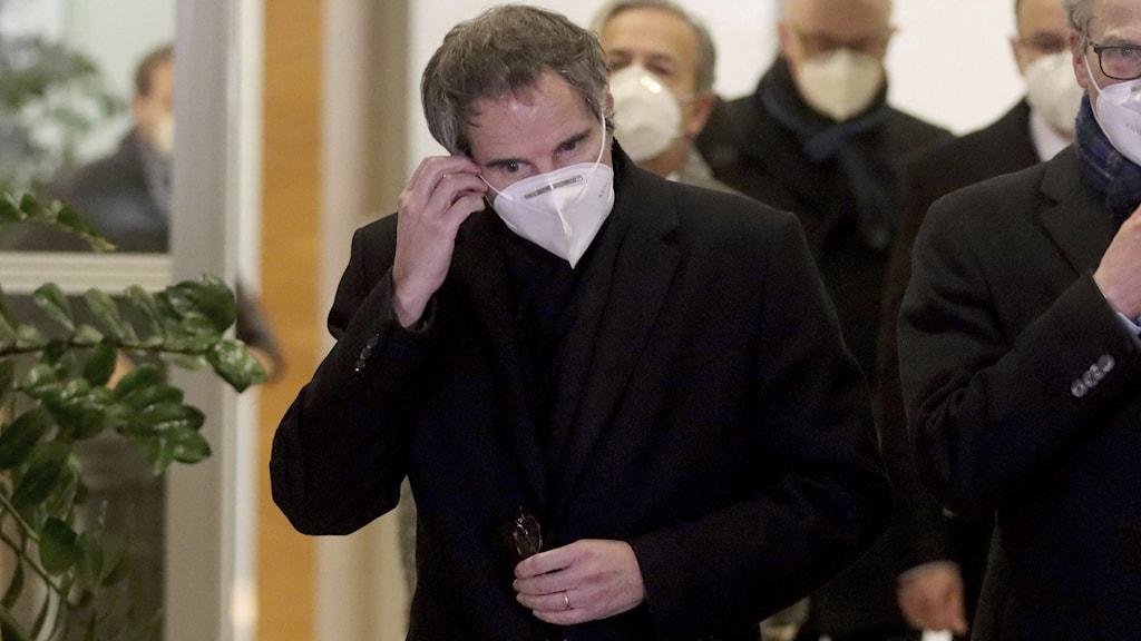 Man i svart rock och vitt munskydd.