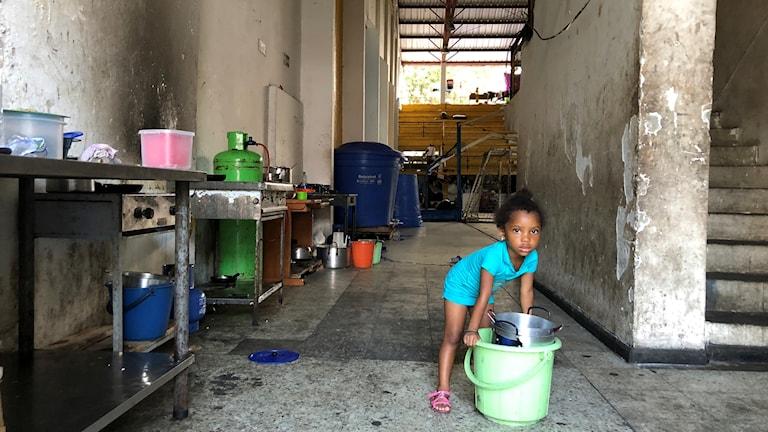En liten flicka hämtar vatten utanför idrottshallen i Buenaventura där de 119 internflyktingarna hysts in. De har flytt från floden San Juan, där ELN-gerillan och paramilitärer strider om det område som Farc-gerillan lämnat.