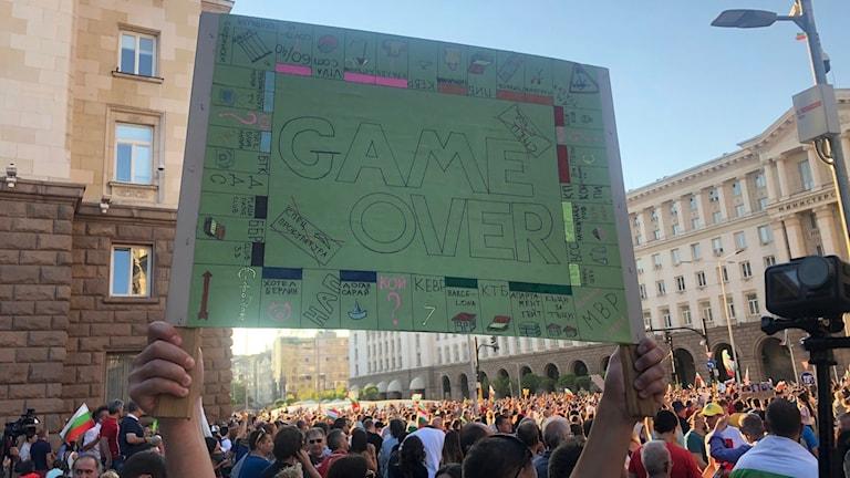 """Folkmassor som demonstrerar. En person håller upp en skylt där det står """"game over""""."""