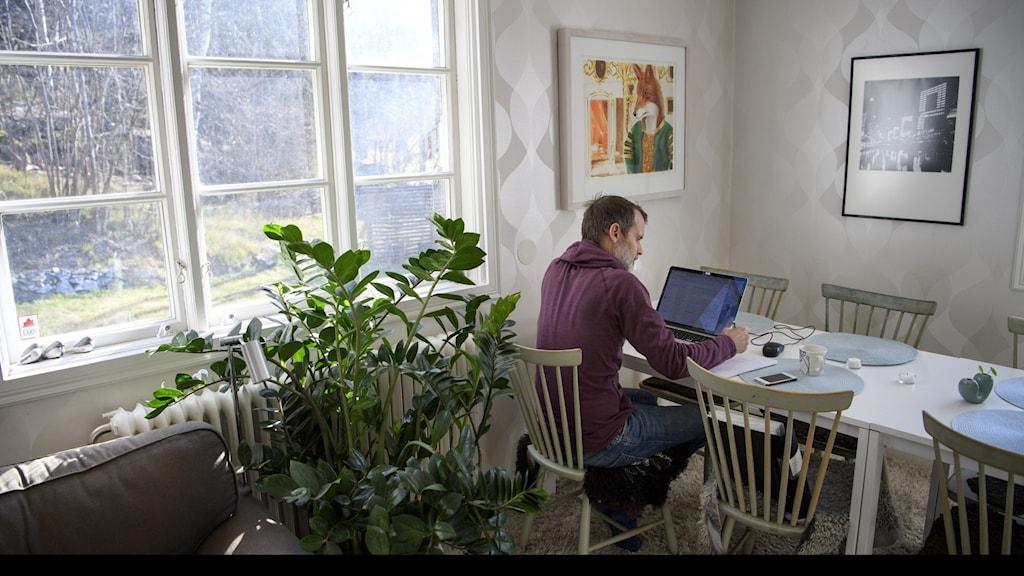man arbetar hemma vid bord med dator