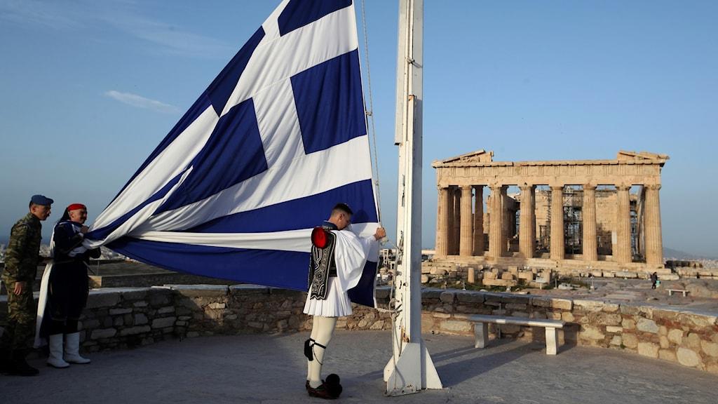 Grekisk flagga hissas vid Parthenon.