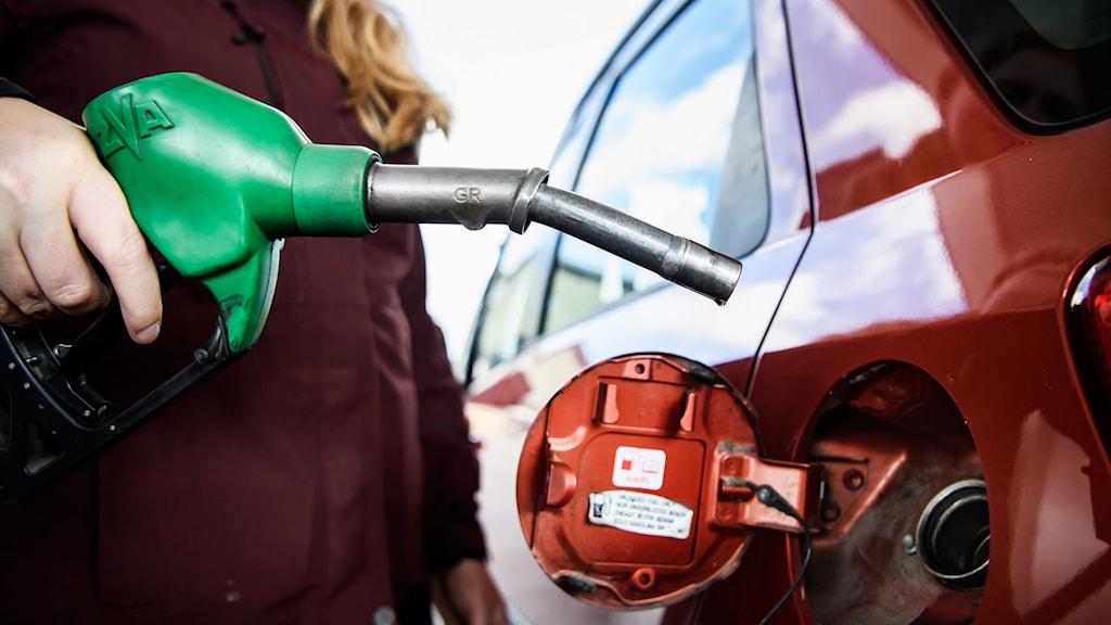 Närbild på en bil med öppet tanklock och en kvinna som står och håller i bensinpump.