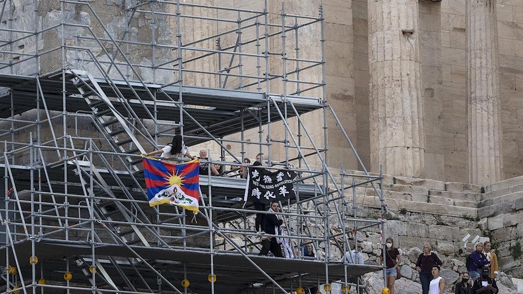 Demonstranter har klättrat upp på byggnadsställningarna vid Akropolis, för att hänga upp protestflaggor mot OS i Kina.