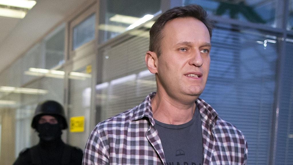 På fotot är Aleksej Navalnyj klädd i en rutig skjorta. Bakom honom står en polis med svart mask för ansiktet och ett vapen.