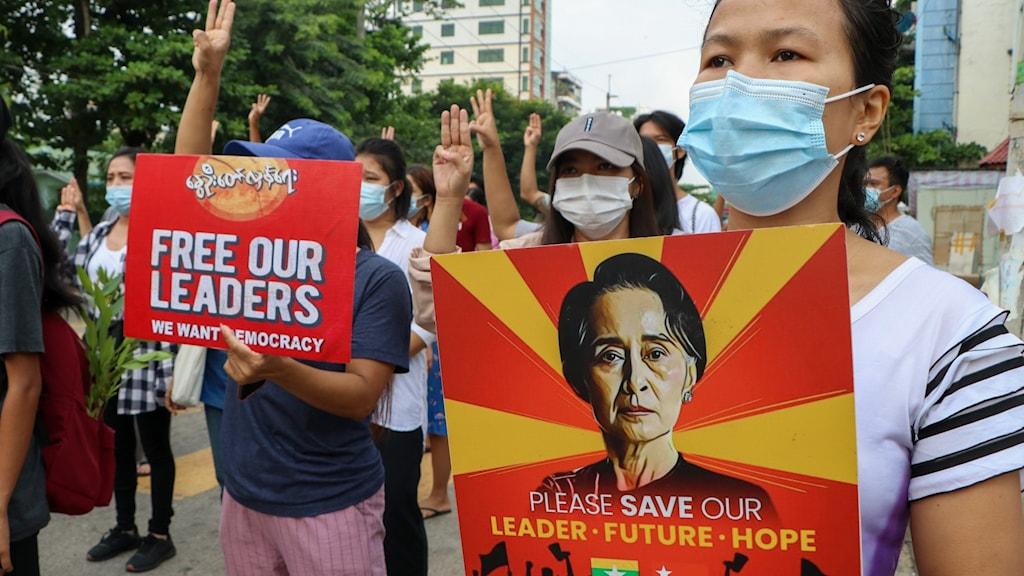 Demonstranter håller bild på Aung San Suu Kyi under en demonstration
