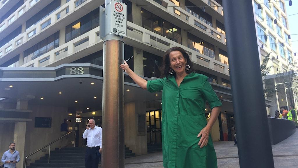 North Sydneys borgmästare Jilly Gibson pekar på en rökförbudsskylt intill ett torg i staden.