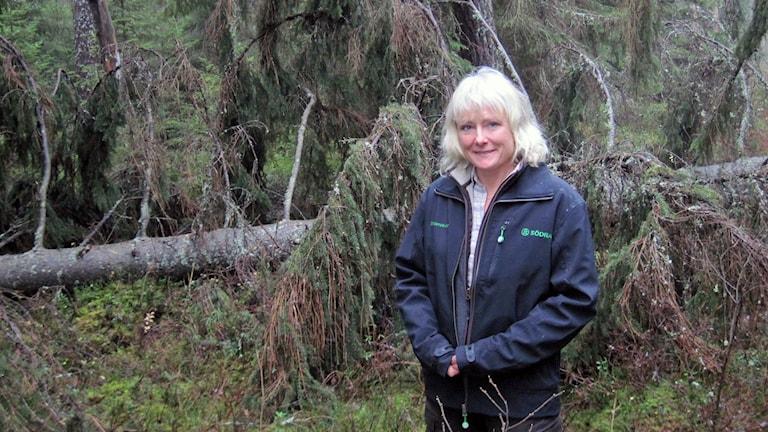 Camilla Logarn har just hår. Hon står ute i sin skog.