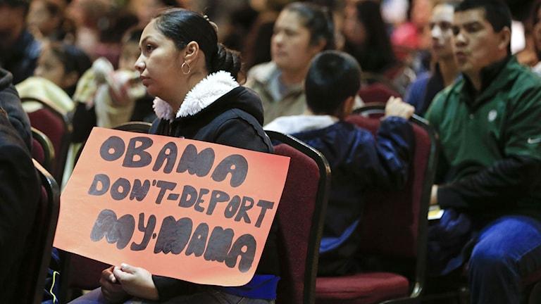 """Kvinna lyssnar på Barack Obamas tal. I händerna håller hon en skylt med orden """"Obama deportera inte min mamma"""". Foto: Mark Humphrey/TT"""