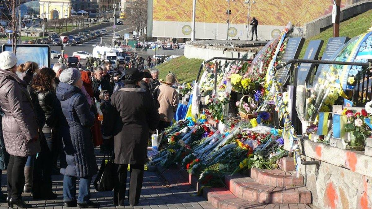 Två stenplattor med inskriptioner med namn på de dödade och mängder av människor som la blommor till minne av offren.