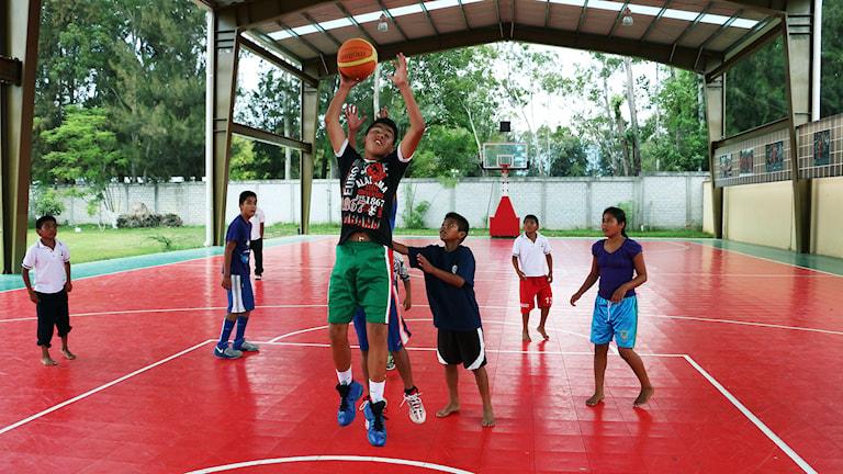 Barn spelar basket.