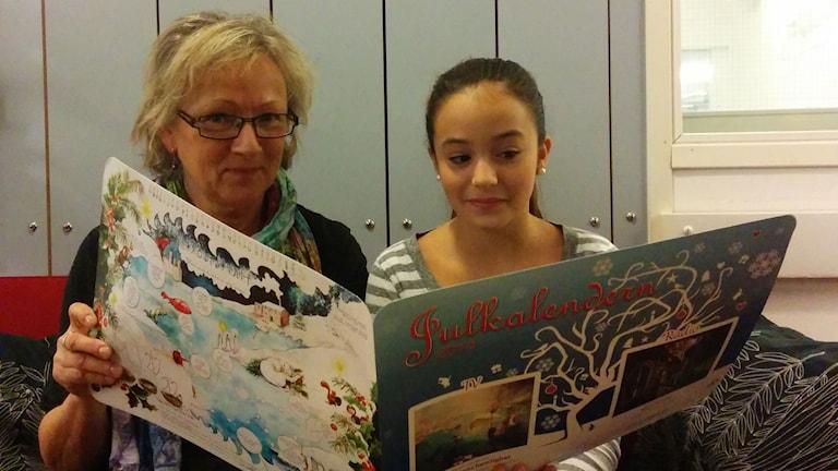 Anna Hernek och Lea Stojanov tittar i årets julkalender. Foto: Karin Albons/Sveriges Radio