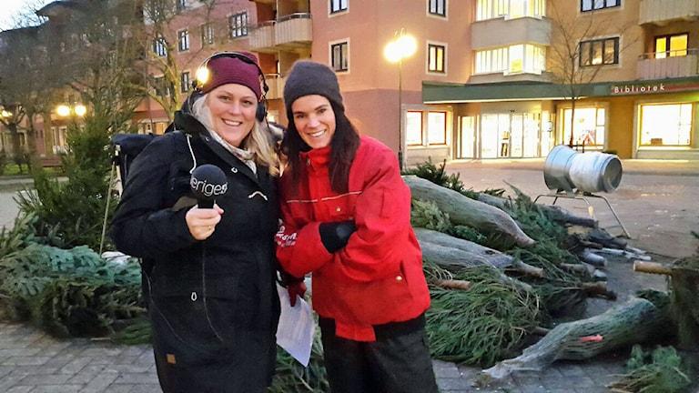 Karin Wirenhed, P1-morgons reporter och Anna Benson, författare, konstnär och julgransexpert. De står framför julgranar på ett torg. Foto: Victor Ubeira/Sveriges Radio