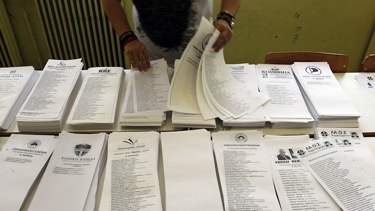 En kvinna organiserar grekiska valsedlar. Foto: TT