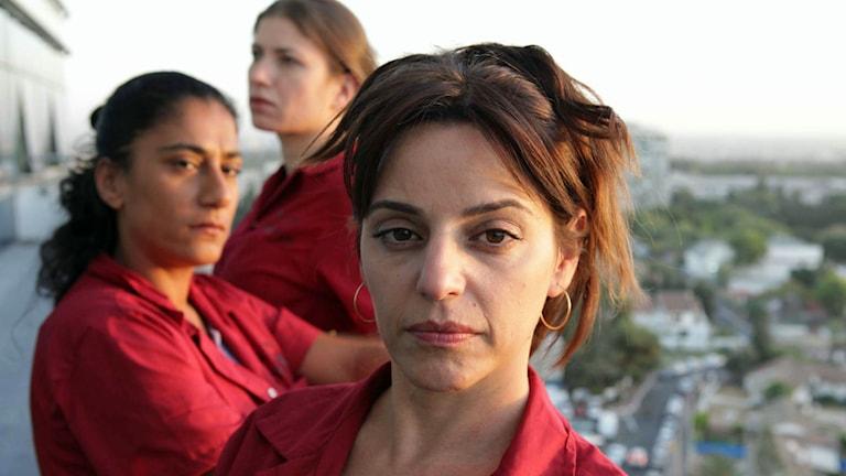 En bild från TV-serien 30 shekels i timmen. Tre rödklädda kvinnor.