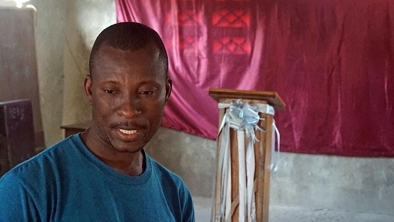 Pastor Baptiste Waller förlorade sin kyrka i skalvet 2010. I lägret har han byggt upp en ny. Han står framför predikstolen. Foto: Tomas Härenstam/Sveriges Radio