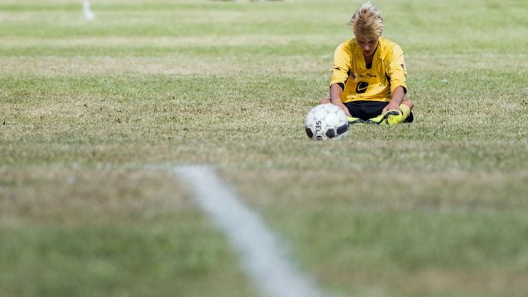 En fotbollsspelare ser besviken ut efter att ha förlorat en match. Han sitter på gräset utanför planen. Foto: Vegard Wivestad Grøtt/NTB scanpix/TT