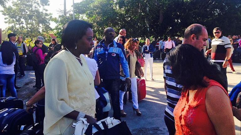 Carida (i vitt) är ledsen över att lämna sina två söner hemma i Havanna när hon nu åker till Brasilien för att arbeta som läkare. Hon står i folksamling med bagage. Foto: Lotten Collin/Sveriges Radio