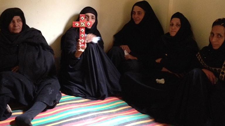 """Mamman till Bishoy och Samuel håller upp ett rött kors o tar emot kondoleanser. """"Mina pojkar åkte till Libyen för att jobba ihop pengar till sina bröllop. Nu firar de bröllop i himlen"""". Foto. Cecilia Uddén/Sveriges Radio."""