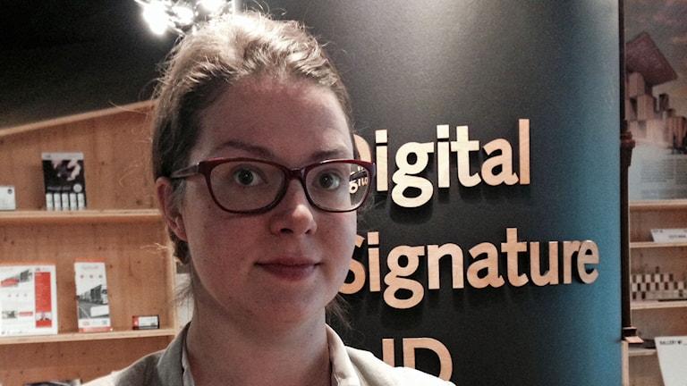 Siret Schutting, kommunikationschef för E-stonia.Hon står framför en pelare med texten: Digital Signature ID. Foto: Karin Wickström/Sveriges Radio