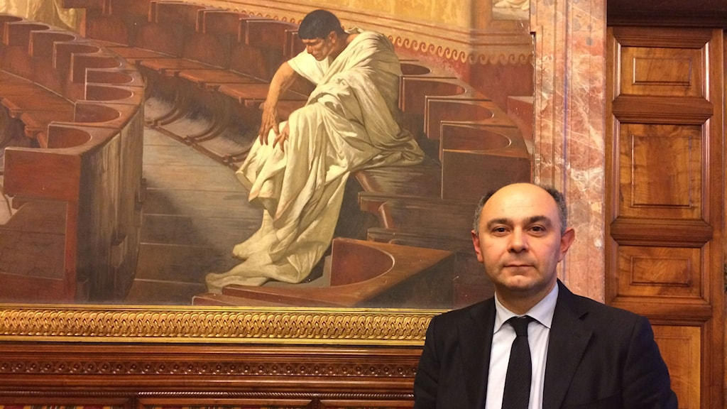 Politikern Peppe de Cristofaro i Senaten sitter med i en kommission om maffian. Han står framför en stor målning med tema med en romare i toga i rätten. Foto: Beatrice Janzon/Sveriges Radio