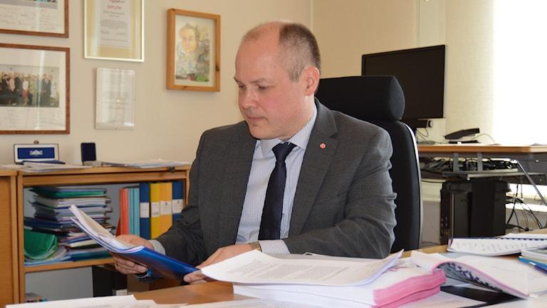 Justitieminister Morgan Johansson läser papper på sitt kontor. Foto: Maria Repitsch/Sveriges Radio.